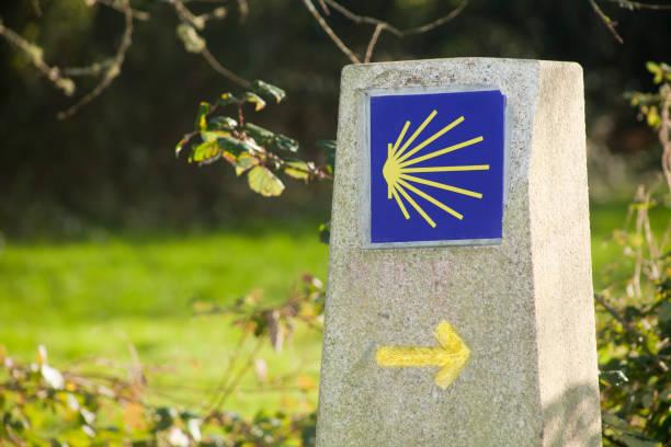 Camino de Santiago, pilgrims shell and yellow arrow on milestone. stock photo