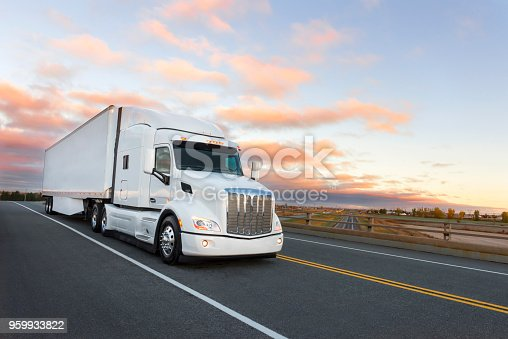 Camion américain sur la route au lever du soleil. Autoroute en arrière-plan.