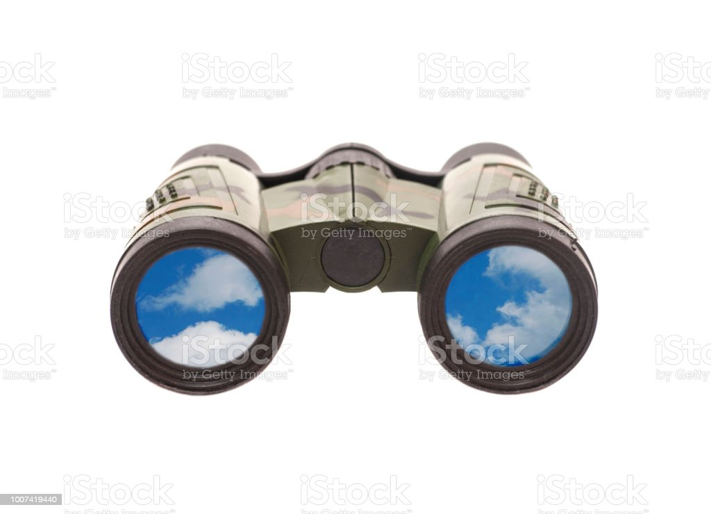 Camouflage binoculars with blue sky and clouds reflection in lenses stock photo