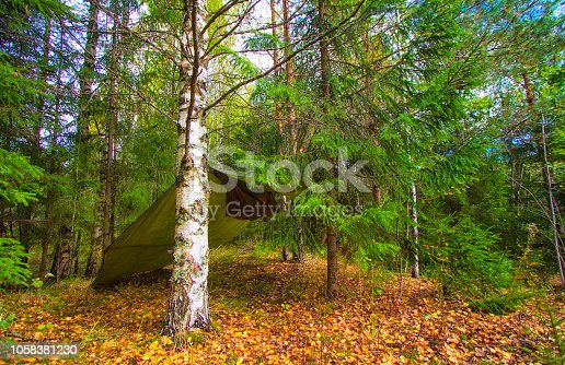 istock camouflage hunter awning ambush deep in the forest. Camping with hammock in the woods. 1058381230