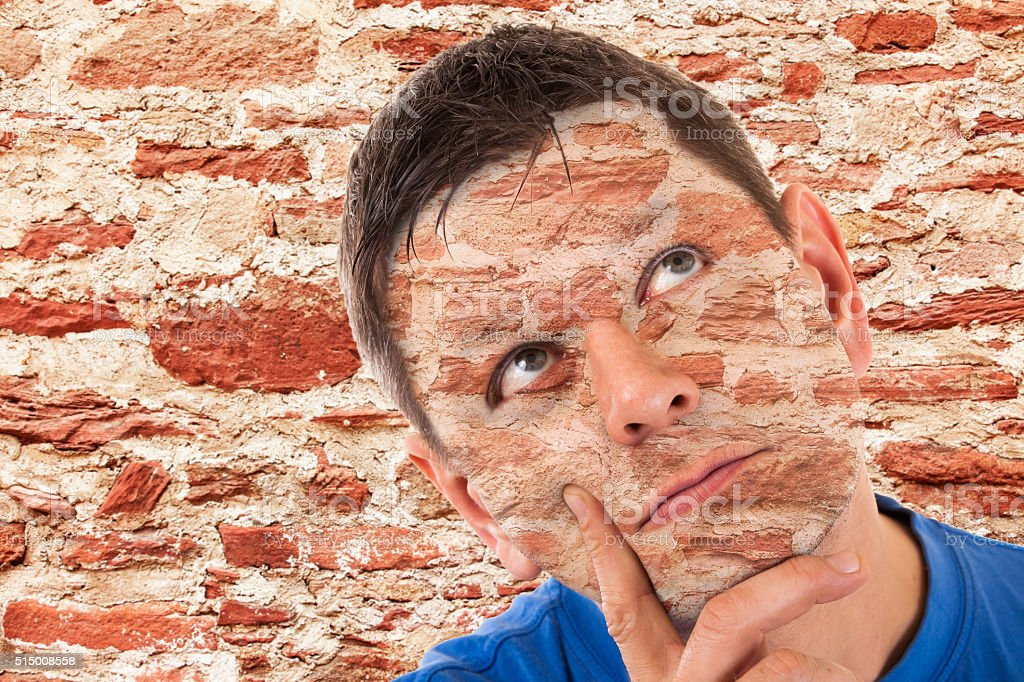 Camouflage -man camouflaged in front of a wall stock photo