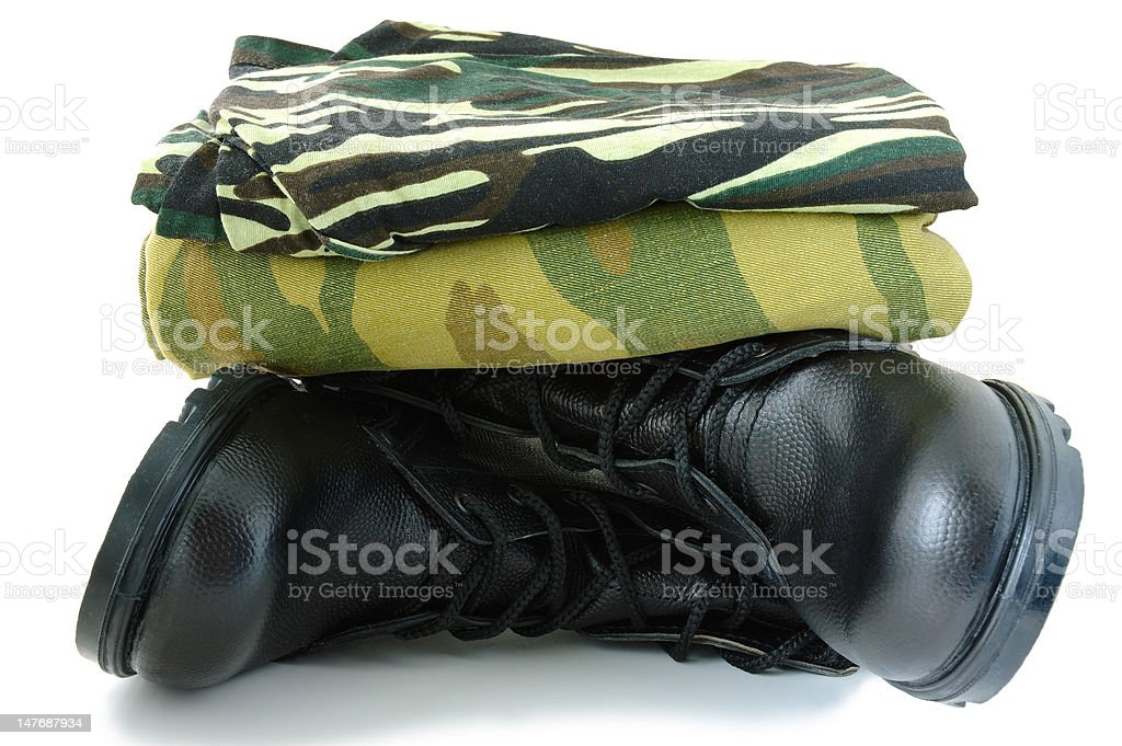 Camouflage uniform and two army boots. royalty-free stock photo