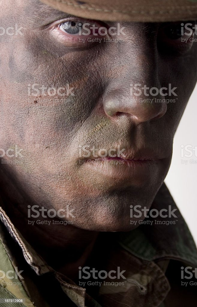 Camouflaged face with pearcing eyes royalty-free stock photo