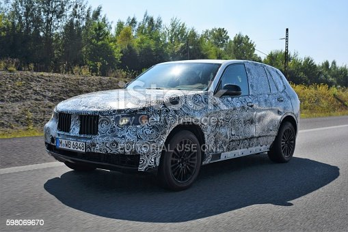 Munich, Germany - August 30th, 2016: The prototype camouflaged SUV from BMW driving on the highway. The new cars are tested and researched for several months (and years) before the introduction on the market. The camouflage hidden the design of newest cars before the market premiere.