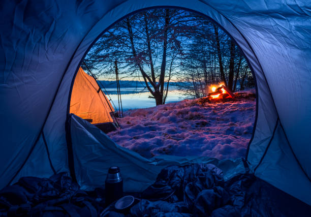 Camp by the lake with campfire in winter at dusk stock photo