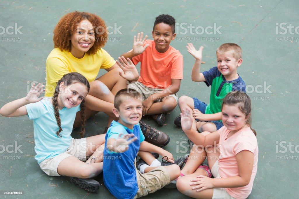 Conseiller de camp, multiethniques enfants assis en cercle - Photo