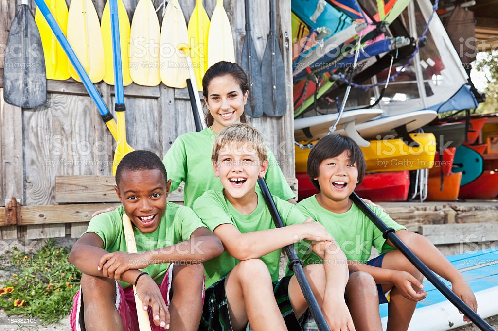 Camp counselor with boys at water sports equipment shack stock photo