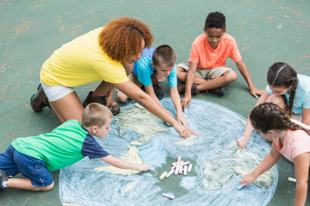 camp counselor with children, chalk drawing of earth - earth day stock pictures, royalty-free photos & images