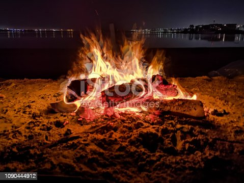 istock Camp fire burning wood on sand at the night 1090444912