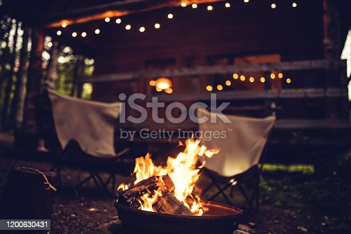 Camp fire and two empty chairs in front of a rustic chalet in Quebec