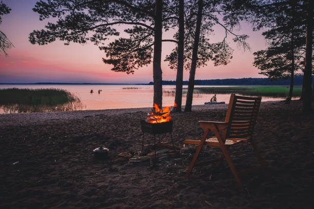Camp fire on sandy beach, beside lake at sunset. stock photo