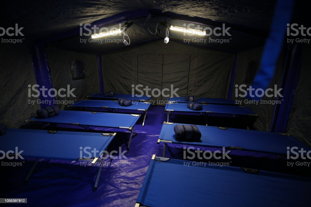 Camp folding cots and sleeping bags are being set up in tents stock photo