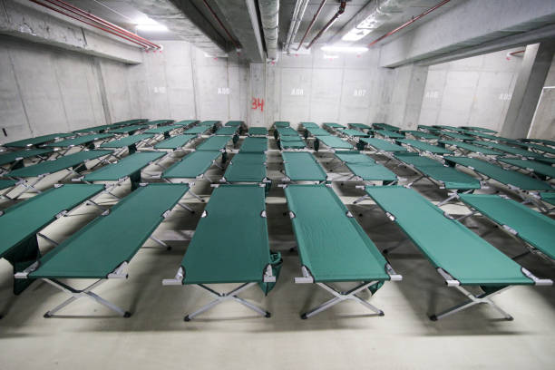 Camp folding cots are being set up in the underground parking of a stadium Camp folding cots are being set up in the underground parking of a stadium and wait for refugees, during the drill of a catastrophic earthquake in the city in which there are many victims bomb shelter stock pictures, royalty-free photos & images