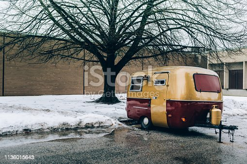 Vintage camp trailer parked on city parking lot in urban Toronto district. Winter, cloudy day.
