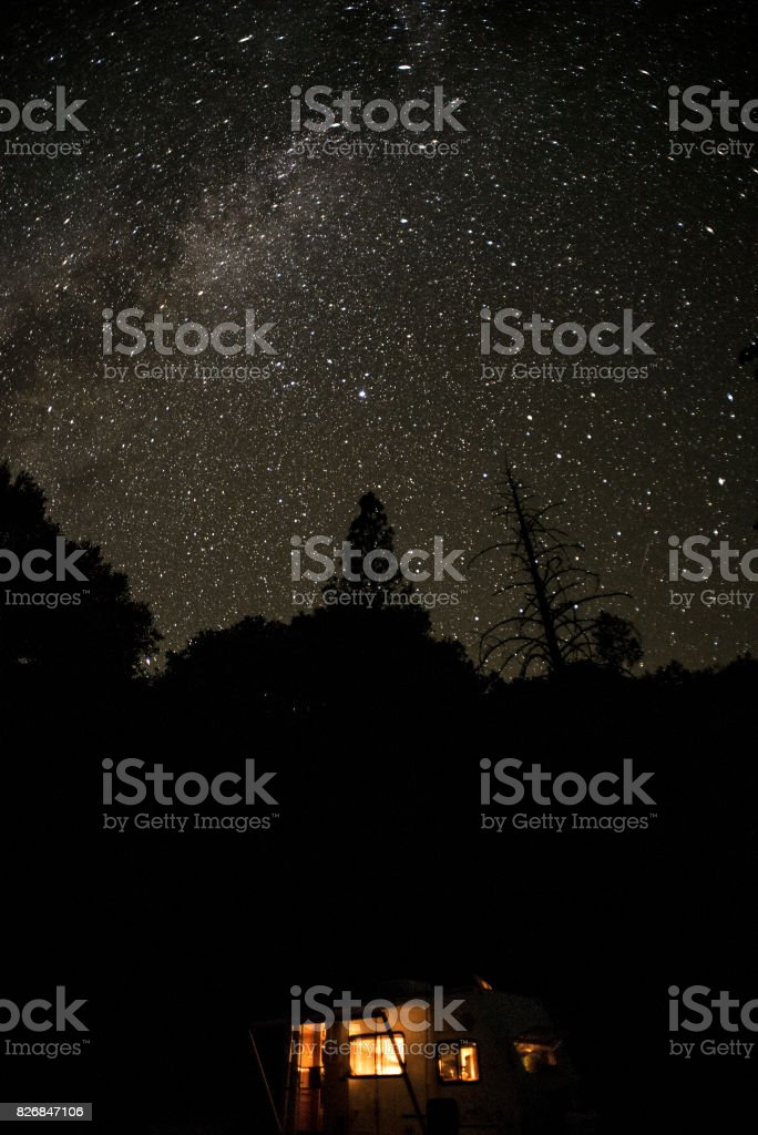 Light from a little trailer under a starry night sky. Northern...