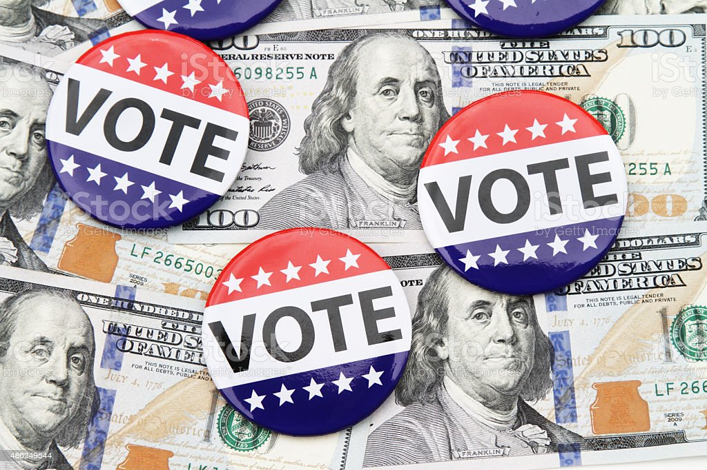 VOTE campaign buttons on top of hundred dollar bills stock photo