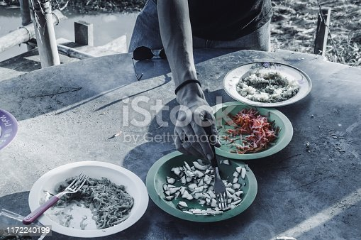 Four plates on dirty surface, each with a type of food and hand picking food on plate with fork