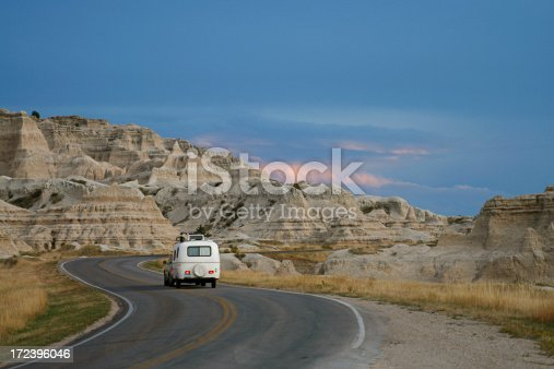 A vehicle towing a retro style camper/trailer through Badlands National Park in South Dakota at sunset.