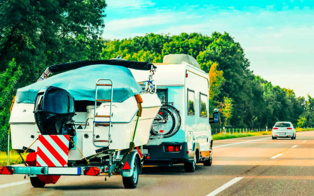 RV Camper Car with motor boat on Road in Switzerland stock photo