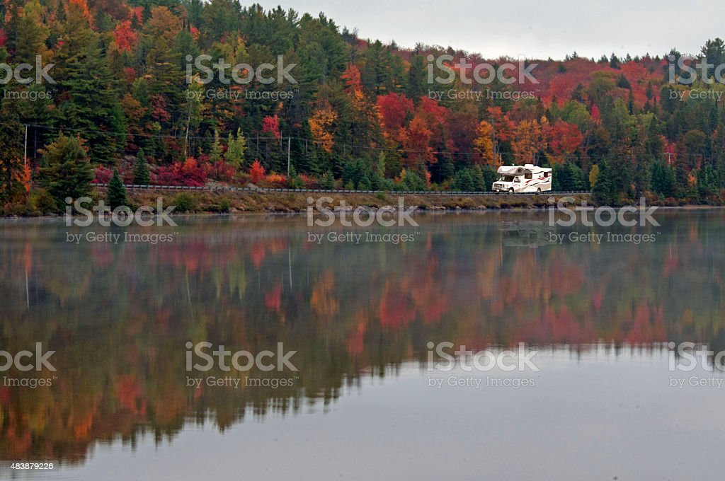 Camper driving through fall forest. stock photo