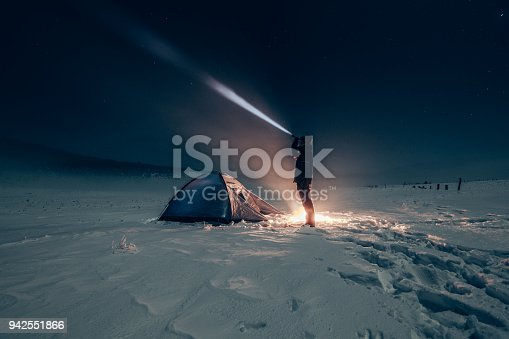 Camper standing in front of his tent with a battery lamp