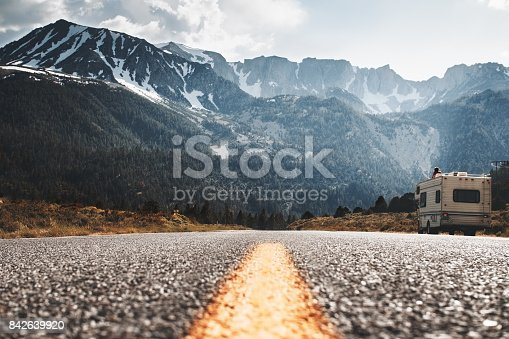 istock RV camper stands on side of road on background of huge mountain. Friends travel to motorhome on mountain road. Travelers rest on sidelines and enjoy mountain view 842639920