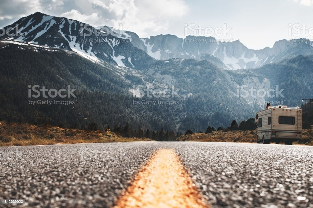 RV camper stands on side of road on background of huge mountain. Friends travel to motorhome on mountain road. Travelers rest on sidelines and enjoy mountain view stock photo
