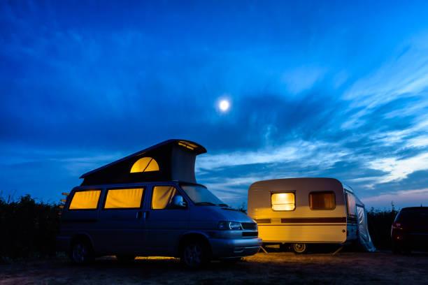 Un camping-car et une caravane illuminé de l'intérieur à la tombée de la nuit avec la lune rougeoyant au-dessus dans un ciel orageux. - Photo