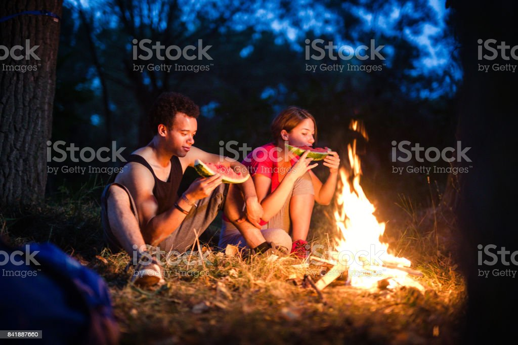 Campers enjoying watermelon near the fire stock photo