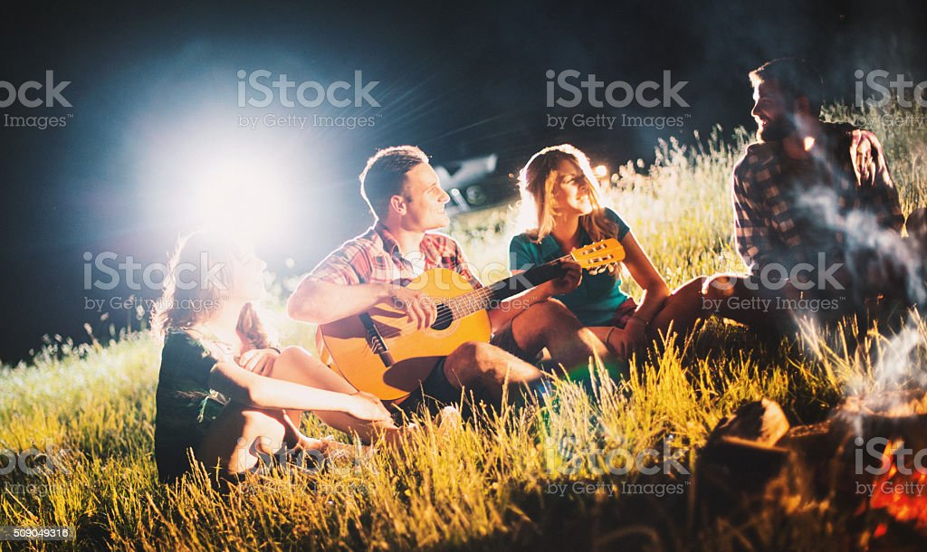 Campers relaxing next to bonfire. stock photo