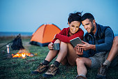Smiling man and woman resting next to the campfire and using digital tablet
