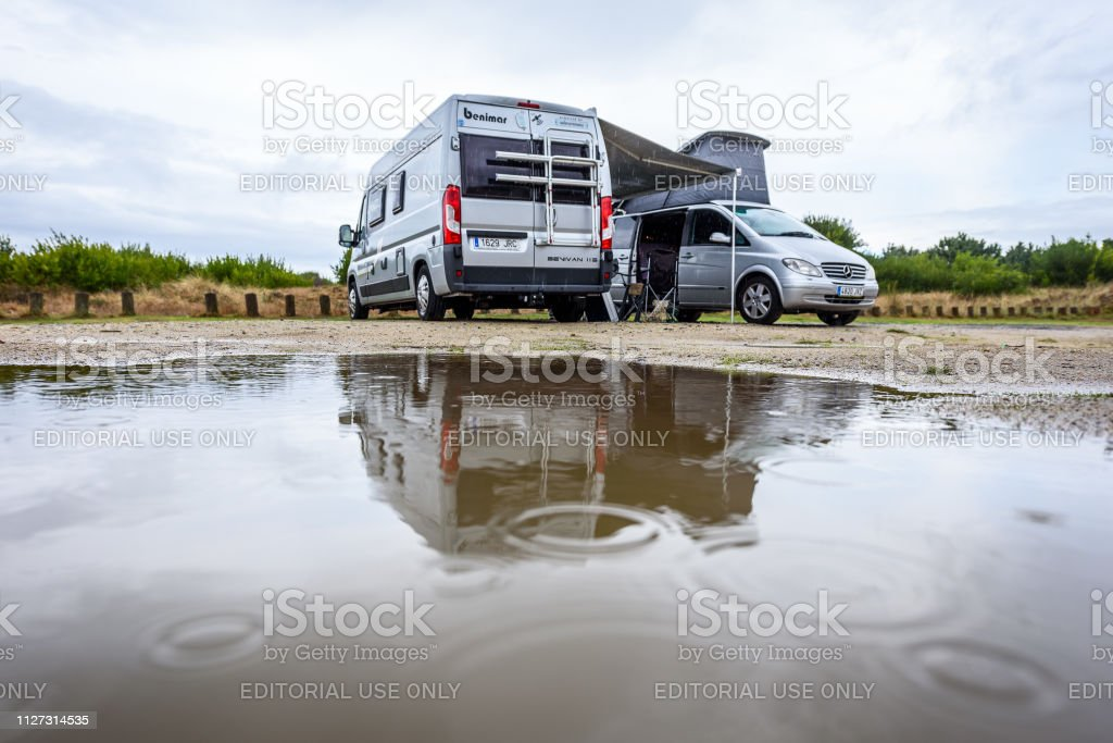 Campervan or motorhome camping on rainy day with rain puddles. Family...