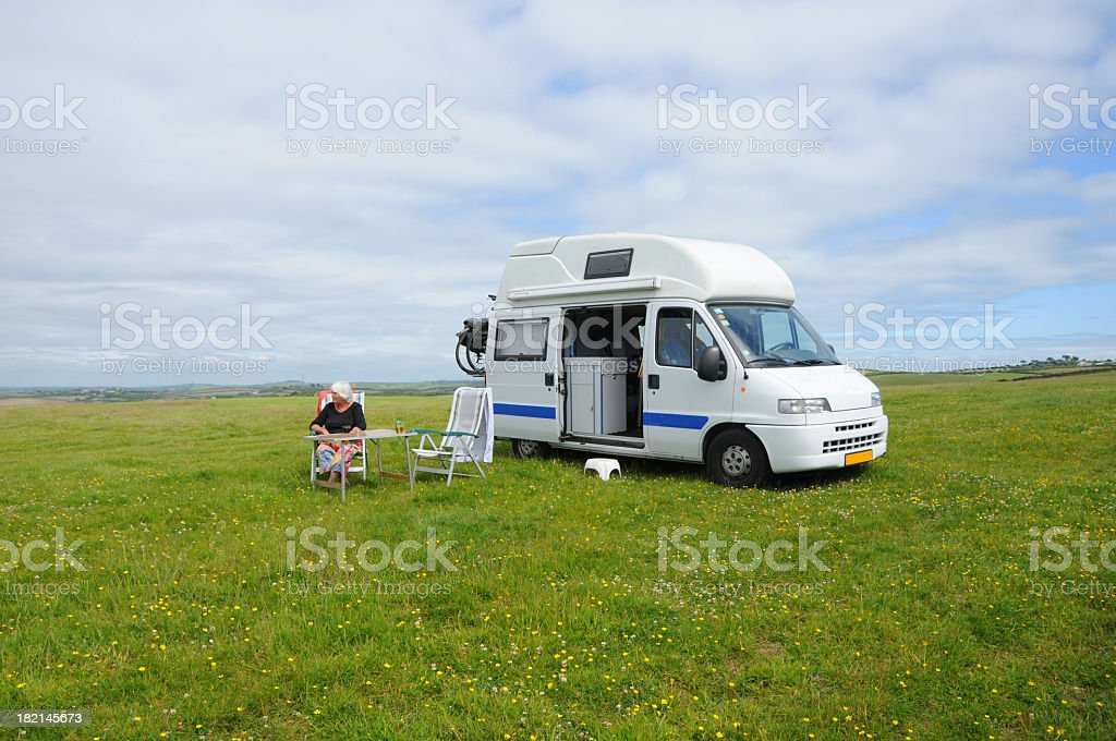 Campervan with senior woman sitting in English meadow. royalty-free stock photo