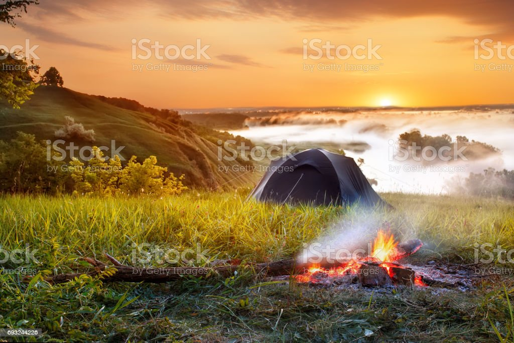 campfire and tent at sunrise stock photo