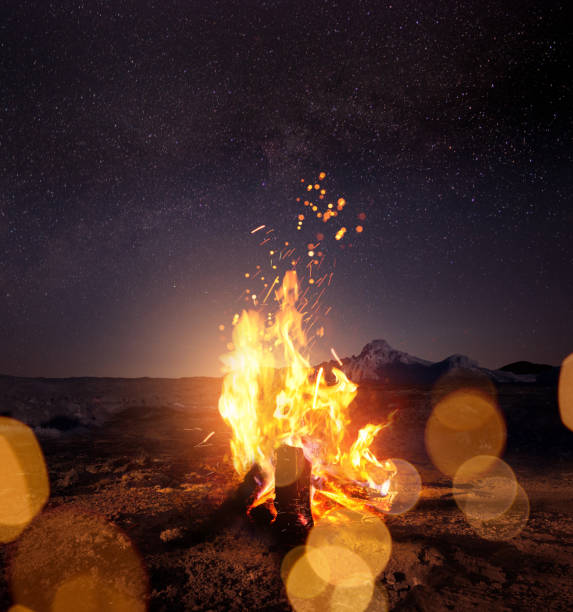 Campfire At Night Watching The Stars Watching the stars around a glowing warm campfire at night. Photo composite. bonfire stock pictures, royalty-free photos & images