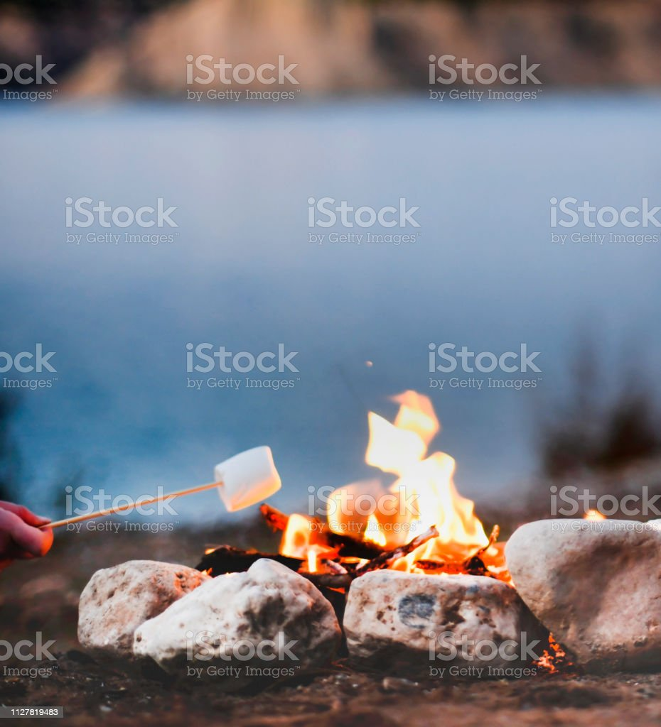 woman\'s hand roasting marshmallows over a campfire in the late summer...