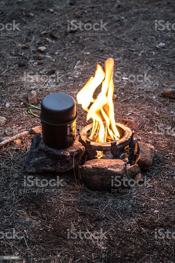 A campfire cookout with cooking pot next to campfire