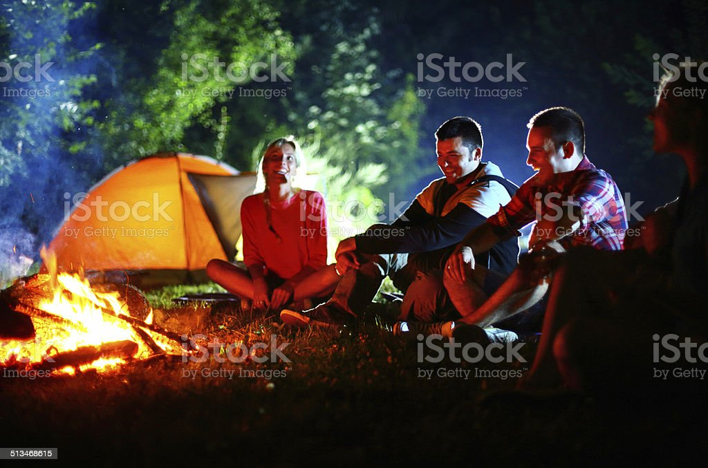 Group of mid 20\'s friends sitting by campfire and having fun on easy...