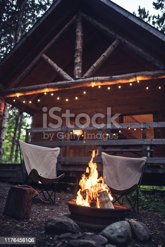 Campfire in front of a rustic house in the forest. There are decorative lights at the entrance