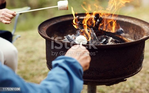 Closeup shot of a senior couple roasting marshmallows while camping in the wilderness