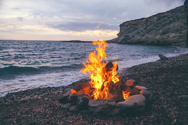Campfire on the beach Summer Camp fire burning in stones on the pebble beach and against sea coast line, rocks and sunset sky. bonfire stock pictures, royalty-free photos & images