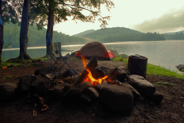 Campfire outside of tent and campsite on a lake in the Adirondack Mountains. stock photo