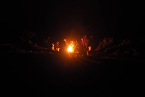 Campfire um ein Feuer sitzen, Lagerfeuer, Nachts, Dunkel, Lichtschein, Frieden log fire stock pictures, royalty-free photos & images