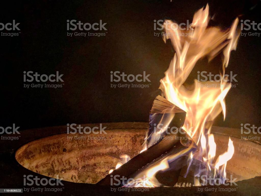 Pile of wood in flames within fire pit