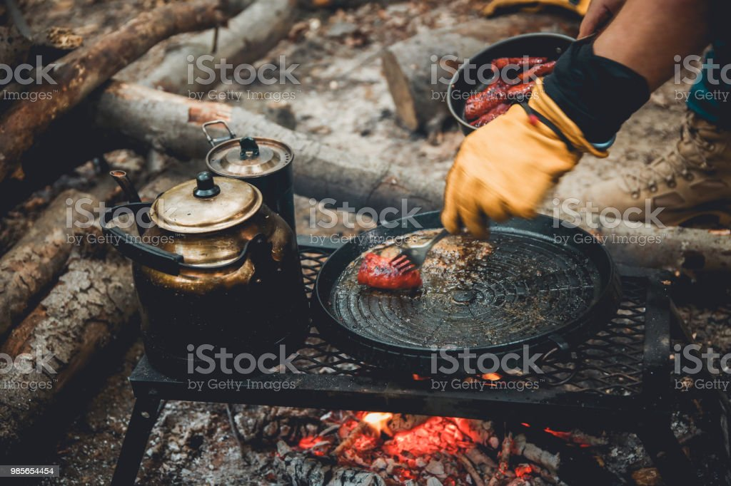 campfire sausage in pan, water bottle and titanium mug near the fire outdoors. bushcraft, adventure, travel, tourism and camping concept. stock photo