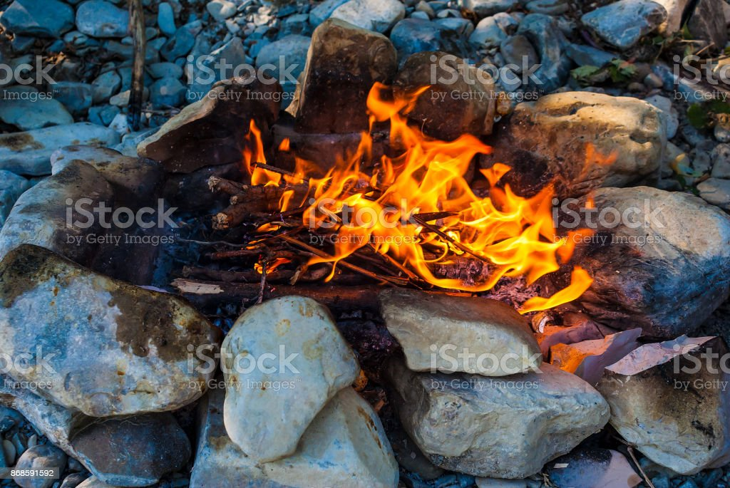 Campfire surrounded by rocks stock photo