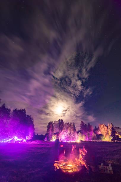 Campfire under moonlight at festival stock photo