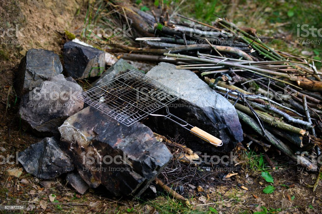 Campfire with empty grilling basket, camping vacation food concept stock photo