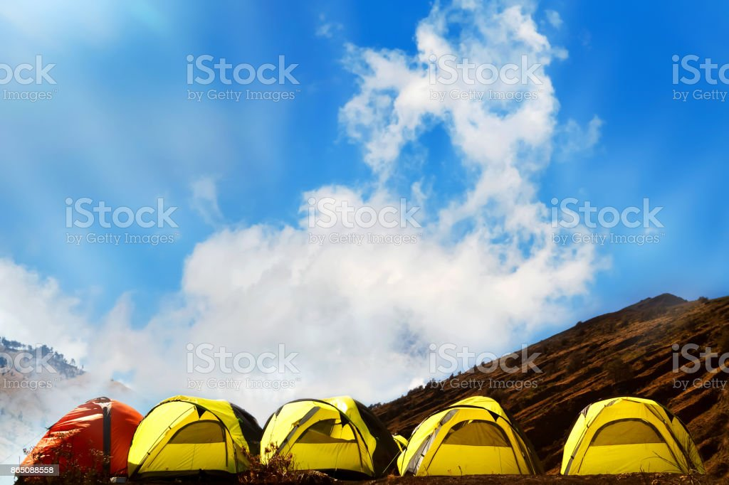 Campground in the mountains. Many yellow adn red tents against the blue sky with amazing clouds. stock photo