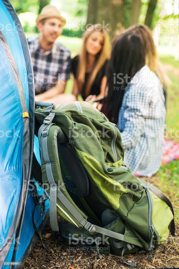 Camping: 4 Friendsnear a Tent. Backpack in Foreground stock photo